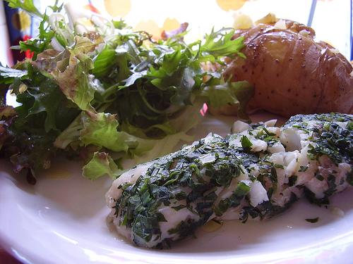 Filé de peixe escalfado com salada verde e batata.